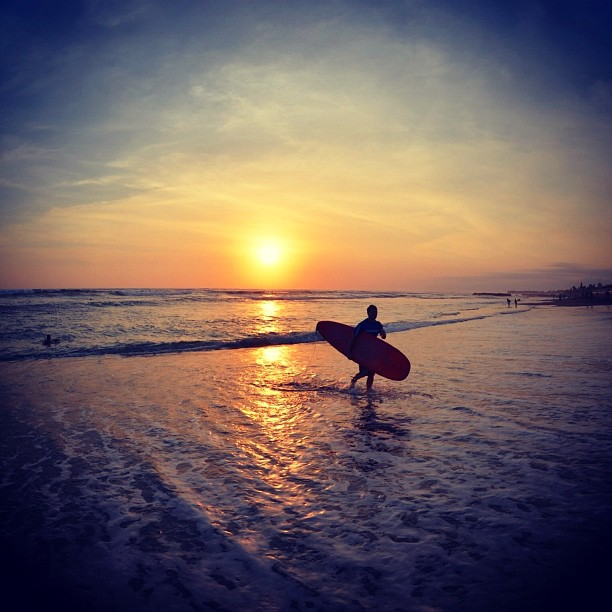 surfing at sunset beach in indonesia